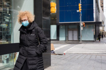 A woman in a mask walks down the sidewalk in Toronto on April 22