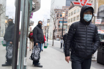 People wearing face masks stand by a TTC stop in Toronto