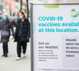 Two people walk past a vaccination sign at a pharmacy