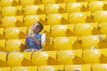 A boy looks at the sky seated alone in yellow seats in All Light, Everywhere, one of the must-see films at Hot Docs 2021