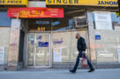 A person walks past a papered up storefront on Queen West in Toronto