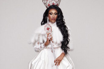 A photo of drag queen Priyanka in white with a crown and scepter.