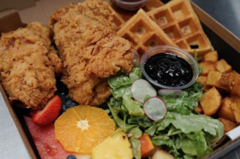 A photo of fried chicken, waffles and salad