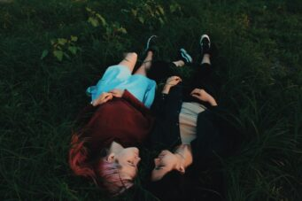 A photo of two people lying close together in a field