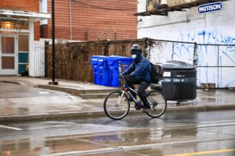 A photo of a person riding their bike in the rain while wearing a mask