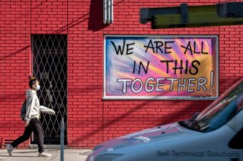 """A photo of a person walking in front of a sign that says """"We Are All In This Together"""""""