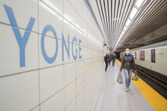 A person in a masks walks on the subway platform at Yonge TTC station in Toronto