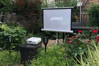 A photo of a projector and screen set up in a backyard