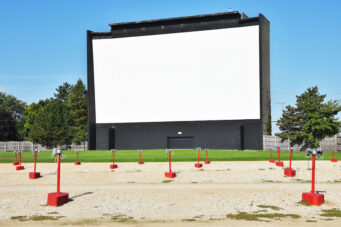 A photo of a drive-in movie theatre with an empty screen