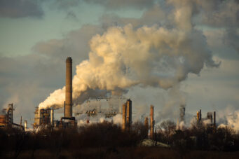 Heavy smoke being released from oil refinery smokestacks in late afternoon.