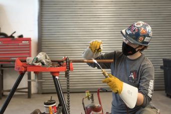 A photo of a trades worker welding a piece of metal