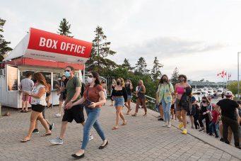Masked fans arrive for a concert at Budweiser Stage.