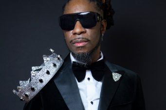 DJ Blackat in a suit and sunglasses with a crown on one shoulder