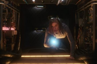 An image of Katee Sackhoff crawling through a starship's duct in the second season of Another Life.